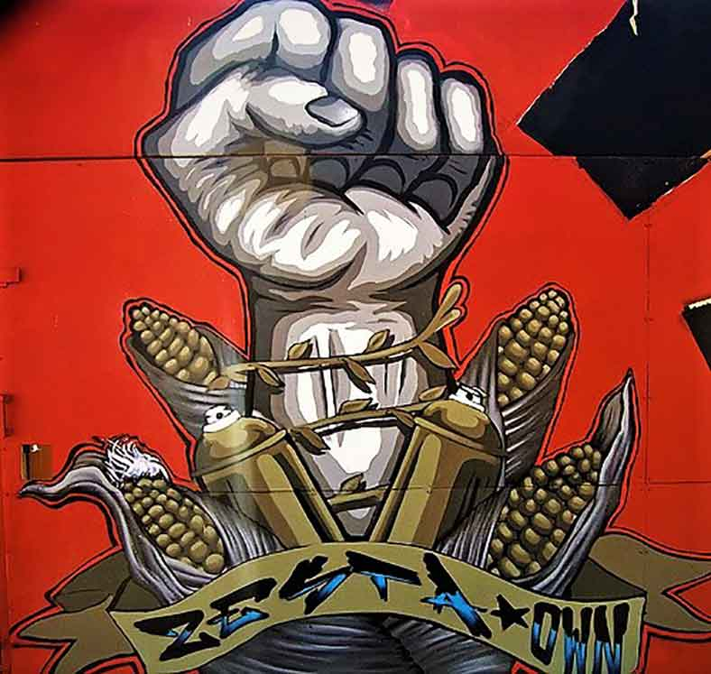 wall mural painting of vector style raised fist with corn cobbs, spray cans and a scroll around it on a red and black background