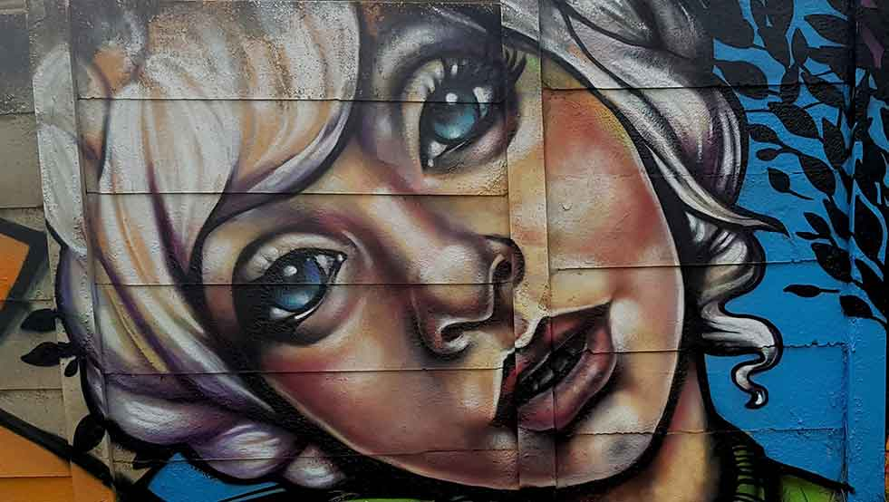 Street art by Page33, painting of a girl with blue eyes and white hair