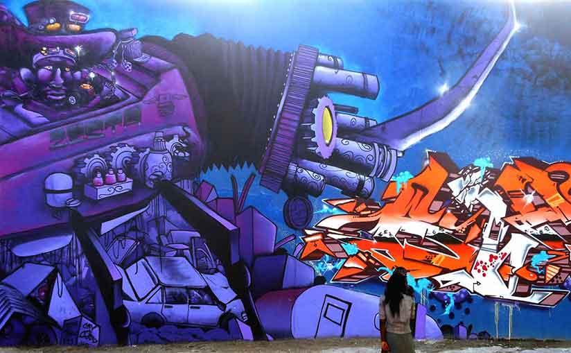Graffiti Street art mural painted by Zesta, purple machine walking over a scrapyard , steampunk street art