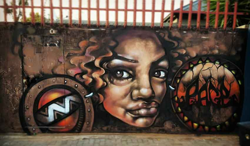 Street art painting of an african lady with big earings, african patterns and sunsent landscape, painted on a gate by Page 33