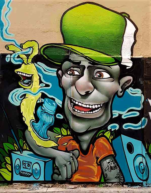 Street art mural graffiti character with green cap, snail and ghetto blaster boom box speakers and tattoos