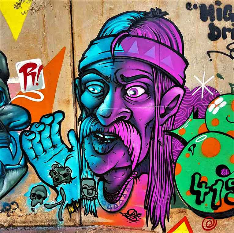 Street art mural, turquoise and purple indian shayman character