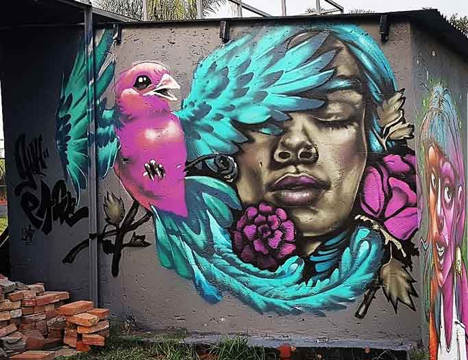 street art wall mural flying birg and womans face, female portrait and bird