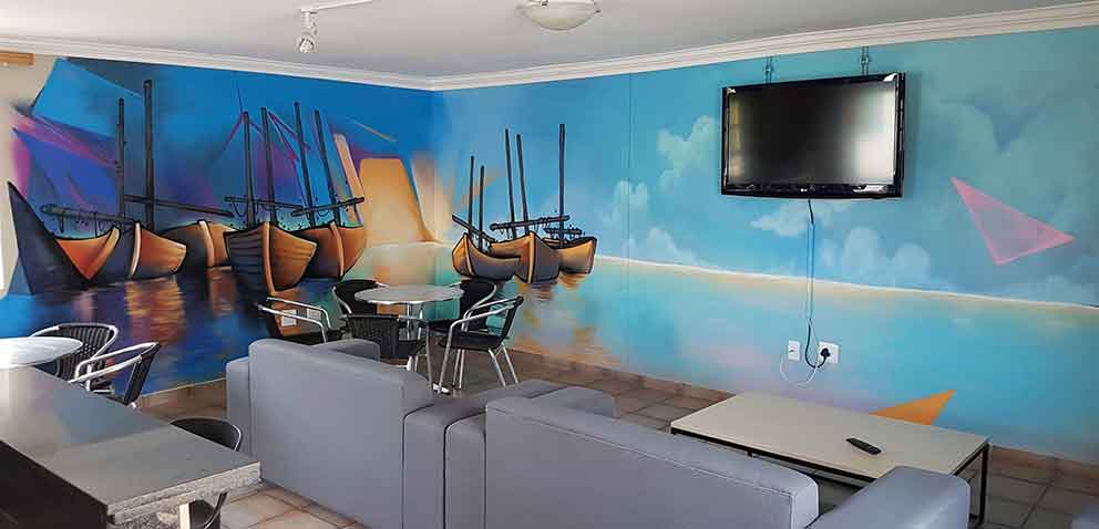 indoor mural in tv room, blue purple and orange, boats on the water sunrise abstract