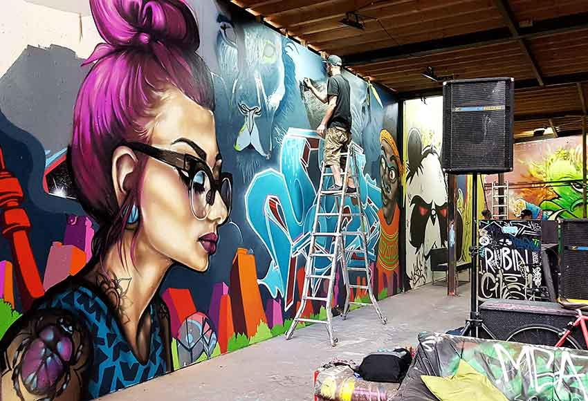 graffiti mural woman with tattoos and glasses, graffiti artist painting on ladder, elephant
