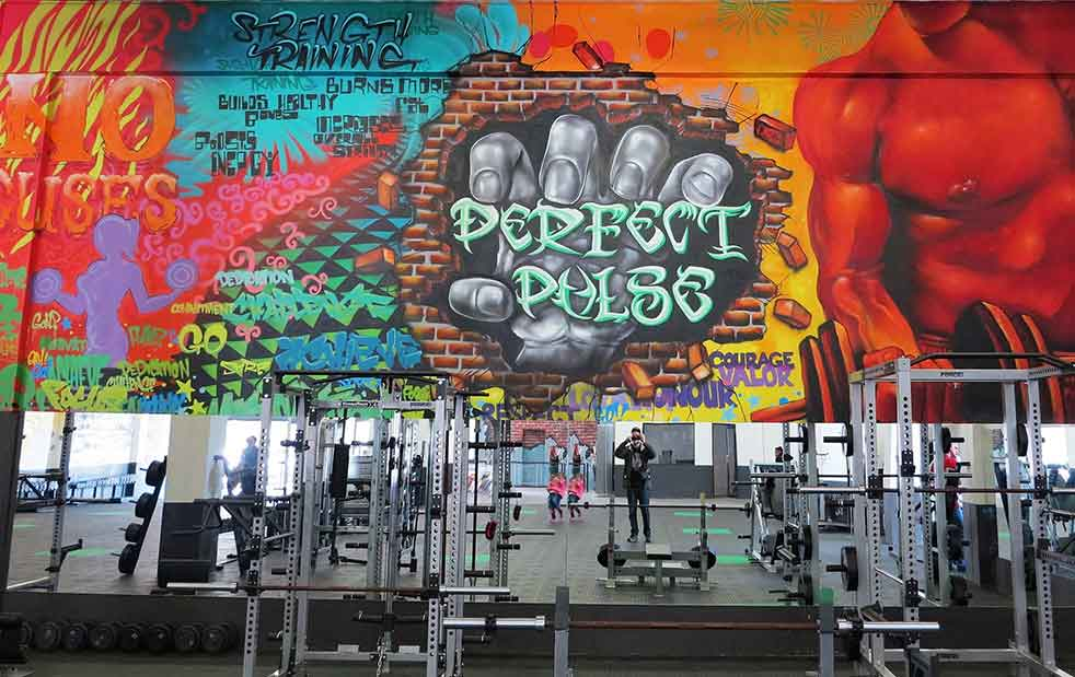 gym mural with graffiti hand breaking through wall, weight lifter muiral, patterns and colour