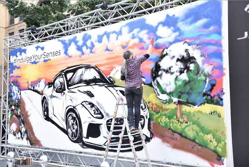 graffiti artist painting mural for Jaguar event
