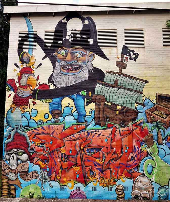 street art mural pirate arguing with his parrot, pirate ship, message in a bottle, octopus on skull, treasure chest