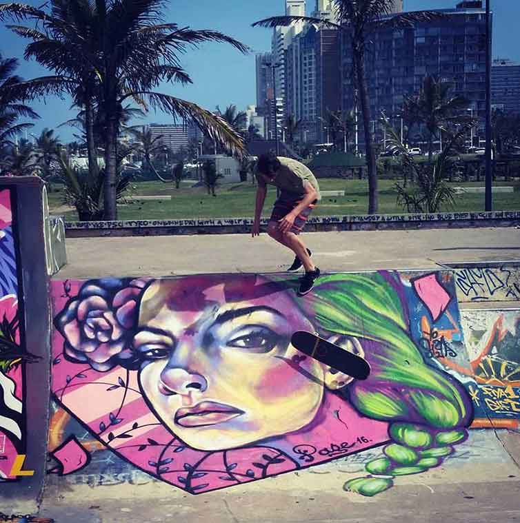 graffiti mural of female portrait at skatepark with boy riding his skateboard on the ramps, palm trees in the background, beach front skate park