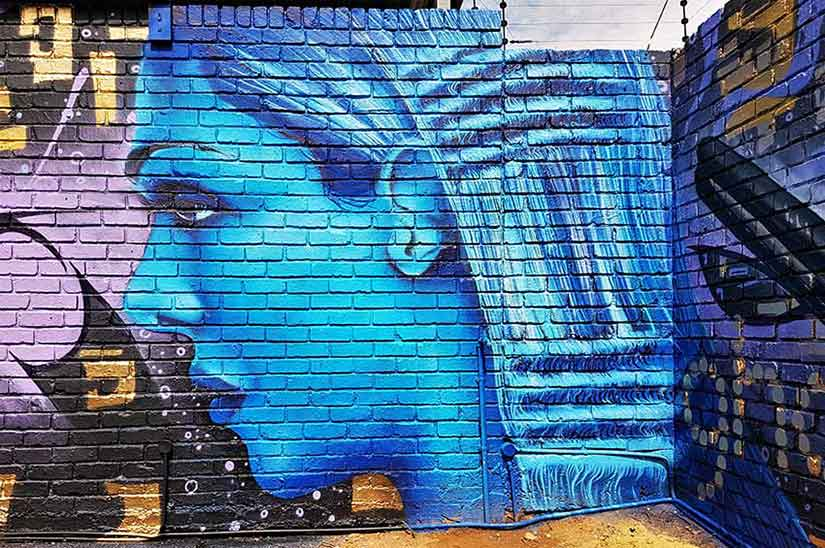 street art mural ghd hair model painted in blue ona a brick wall