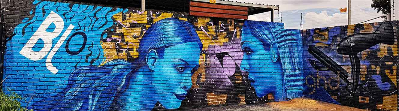 ghd blo graffiti murals blue female models with a hair drier and straightener