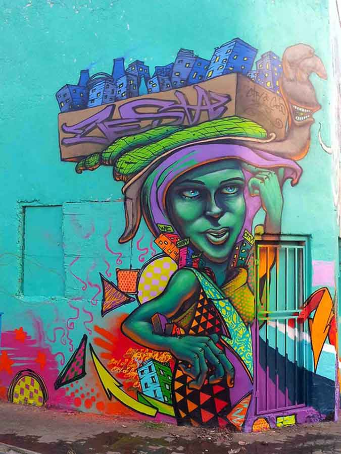 street art mural of african lady carrying a box on her head with a snail and a city in the box, entitled we carry the city, vibrant african patterns
