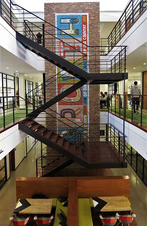 office mural saying growth on a brick wall with a freestanding staircase in front of it, interior design art