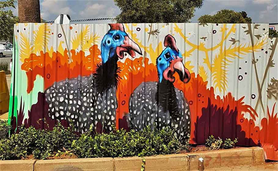 graffiti painting of guinea fowls on building site hoarding