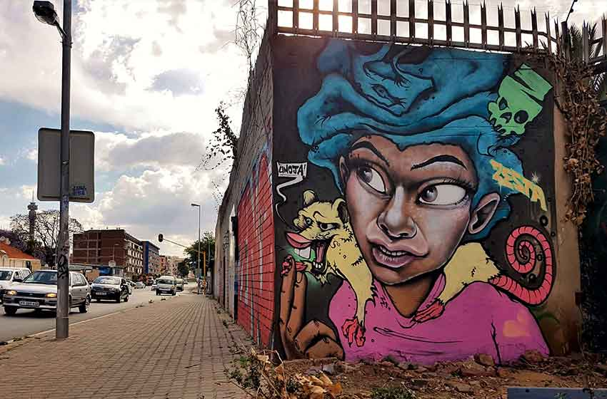 Street art mural next to busy street, female charater, afro and white rat on her shoulders saying umoja - the spirit of togetherness