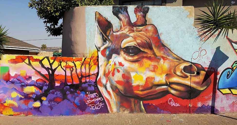 street art mural giraffe and landscape painting on a wall on the side of the road