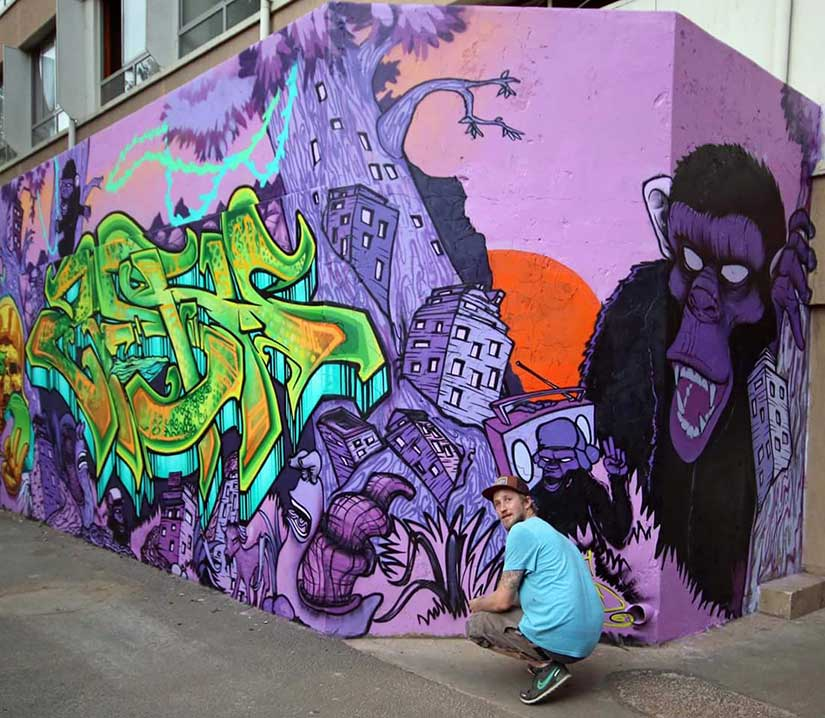 graffiti artist crouching in front of his mural puple, green, black and orange street art