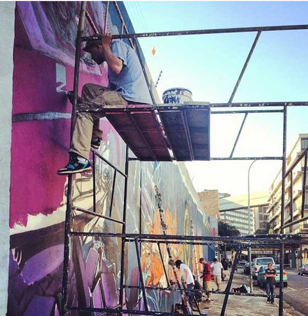 graffiti artist sitting on scaffolding painting graffiti