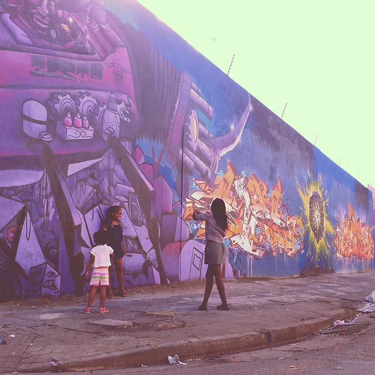 three girls standing in front of a graffiti mural taking photographs of eachother