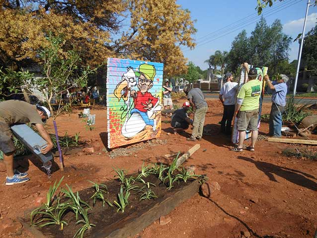 geurrilla gardening project with people planting trees and flowers and installing art installations
