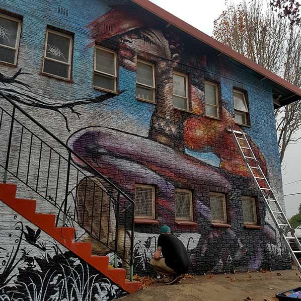 street art mural lady crouching, artist crouching, ladder leaning againts graffiti wall.