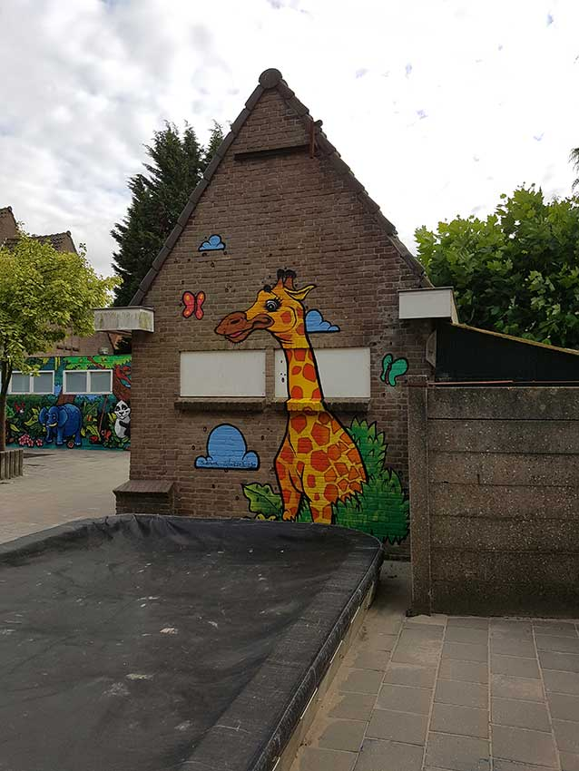 kids mural of a giraffe next to a sand pit with forest mural in a playground