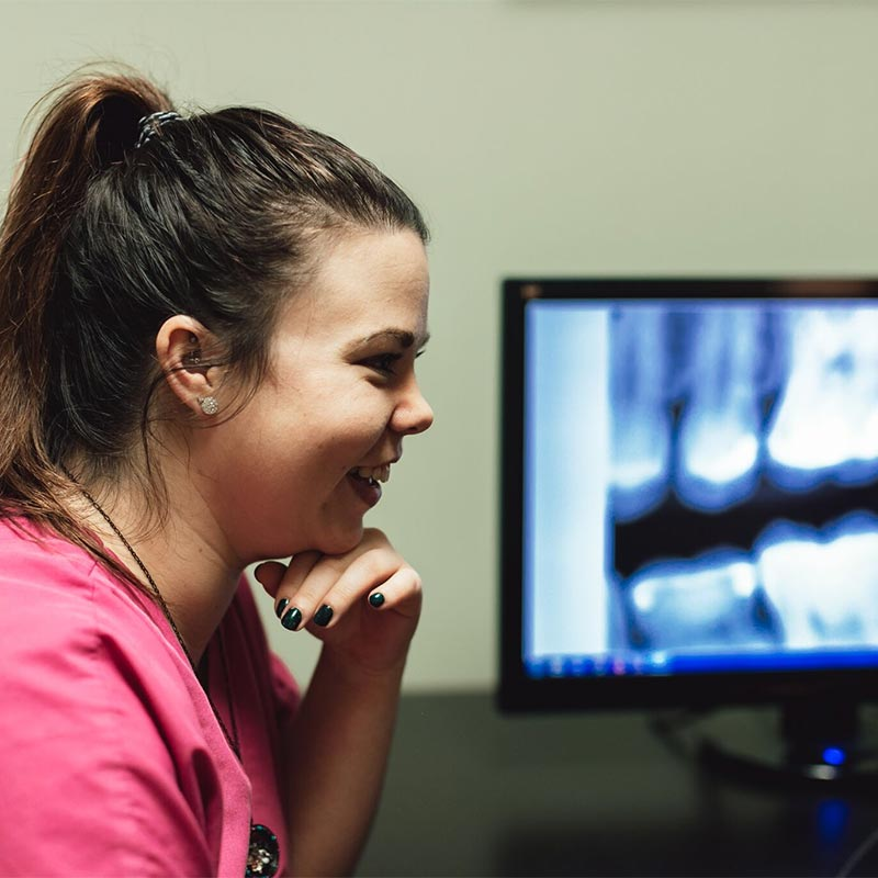 Photo of staff member looking at an x-ray scan on a computer