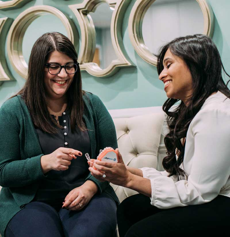 Photo of Dr. Gi Gi Paralkar and a patient looking at an Invisalign® model