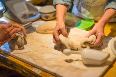 Executive Chef Cathy making sourdough bread dough from scratch, helped by another guest.