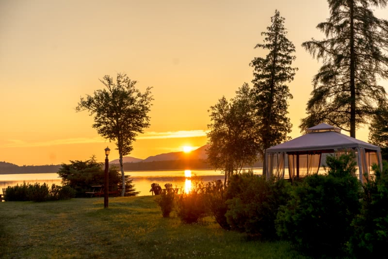 A lakefront sunset at the Lake Clear Lodge with gazebo in the foreground and the sunsetting over St. Regis Mountain in the background reflecting off Lake Clear.