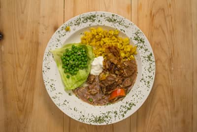 Fresh-cooked Stroganoff at the Lake Clear Lodge and Retreat on a wooden background, served with farm-fresh peas, homemade spaetzle noodles, and sourcream.