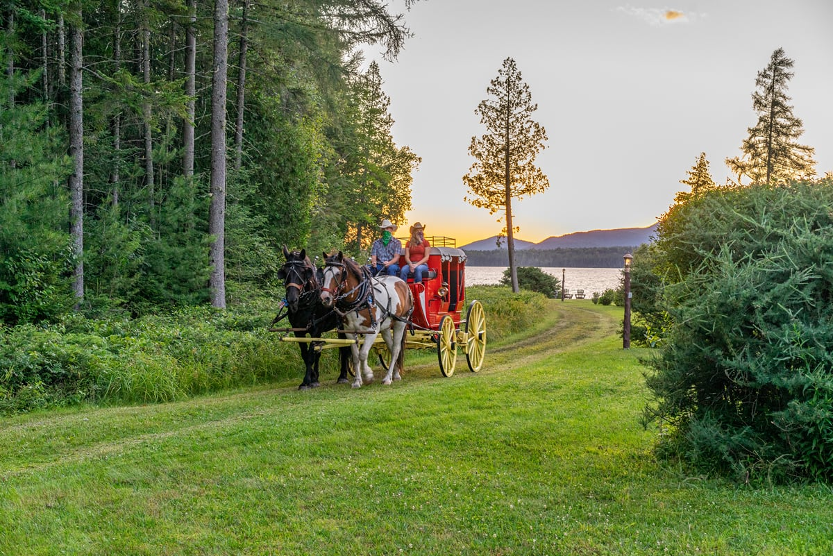 Draft horses pulling an 1850s Stagecoach along a grassy path with mountain-lake sunset in the background.