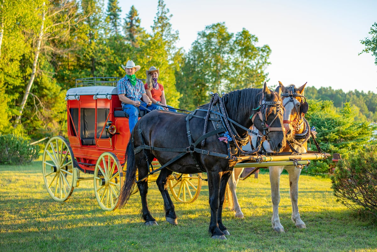 An 1850s Henderson Stagecoach with Draft Horse team illuminated by a bright mountain-lake sunset in Lake Clear, NY.