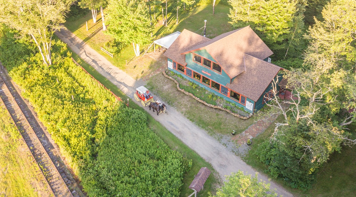 Aerial of Percheron Draft Horse Team Jasper and Fly pulling the 1850s Henderson Stagecoach at the Lake Clear Lodge & Retreat, next to the Lake View Retreat Center with tented patio.