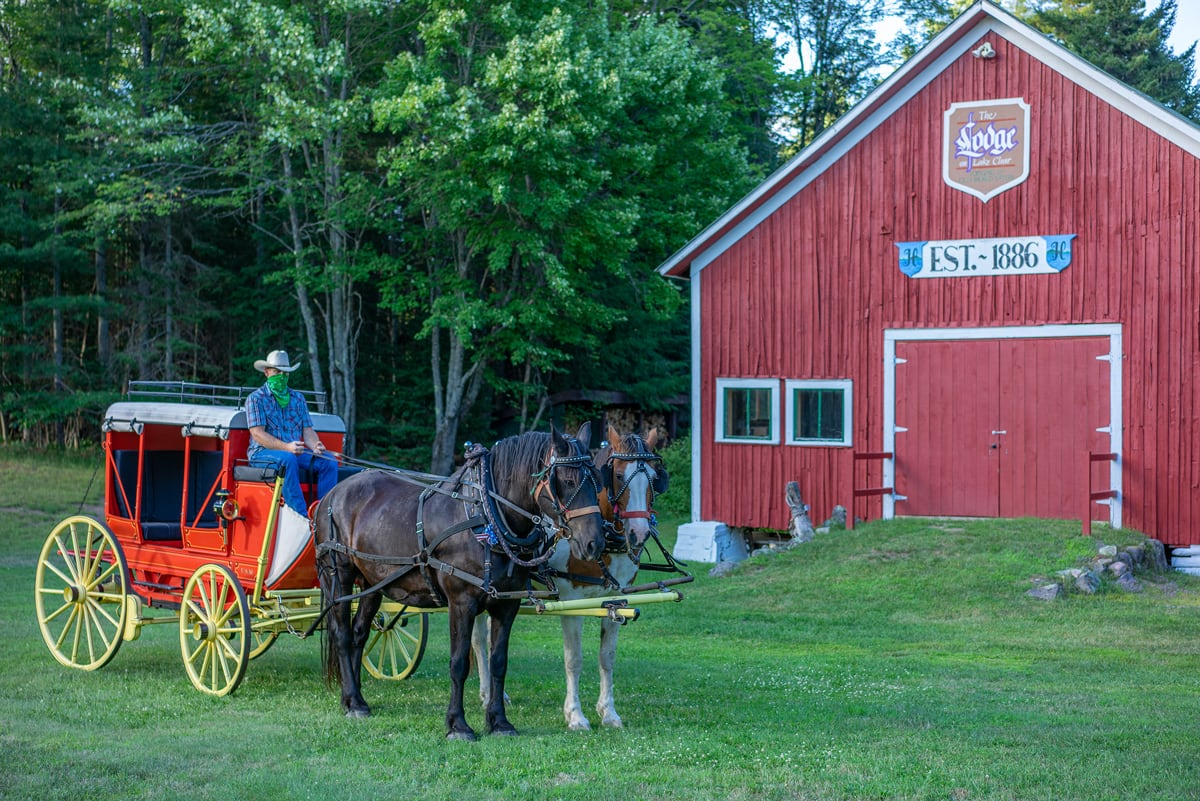 Percheron Draft Horses Jasper and Fly in front of the original 1800s Stagecoach Barn at the Lake Clear Lodge & Retreat. The draft horses have an 1850s Henderson Stagecoach in tow.