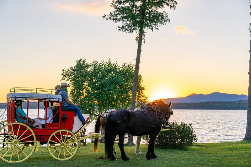 1850s Henderson Stagecoach with Percheron Draft Horses Jasper and Fly at the Lake Clear Lodge Lakefront during sunset.