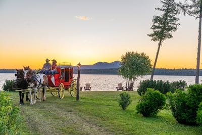 Sunset Stagecoach Ride at the Lake Clear Lodge. A Henderson stagecoach is pulled by Percheron Draft Horses at the Private Beach at the Lake Clear Lodge. Guests enjoy a sunset view from inside the stagecoach.