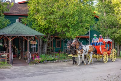 Our 1800s Henderson Stagecoach with Percheron Draft Horses from Lucky Clover Sleigh Rides passes in front of the 1886 Main Lodge at the Lake Clear Lodge & Retreat.