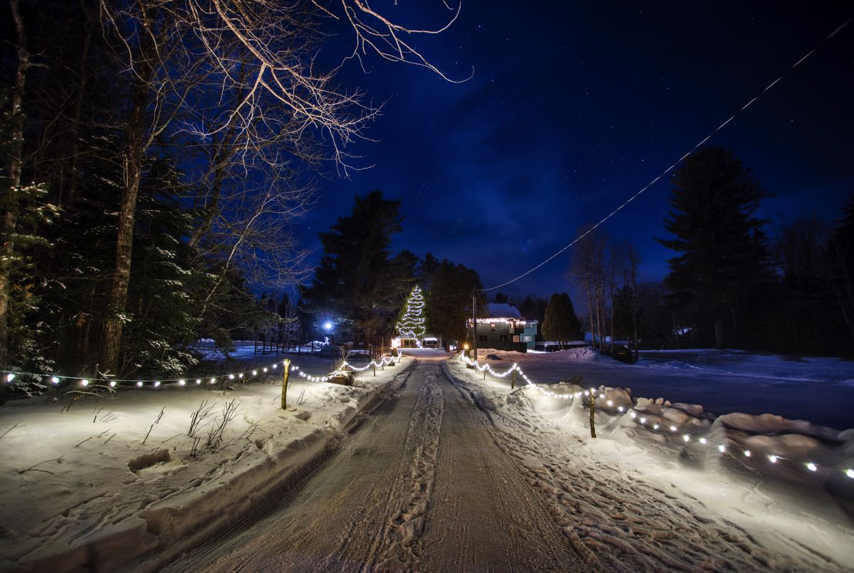 The 1886 Main Lodge in the snowy winter months with a Christmas light-lit driveway.