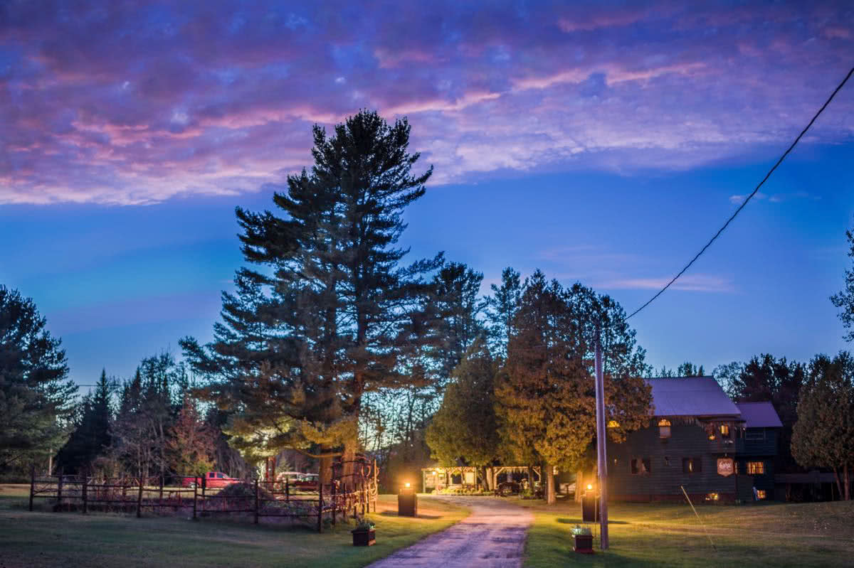 A colorful sky behind the 1886 Main Lodge in the summer months, showing the rustic entrance and driveway to the Lake Clear Lodge.