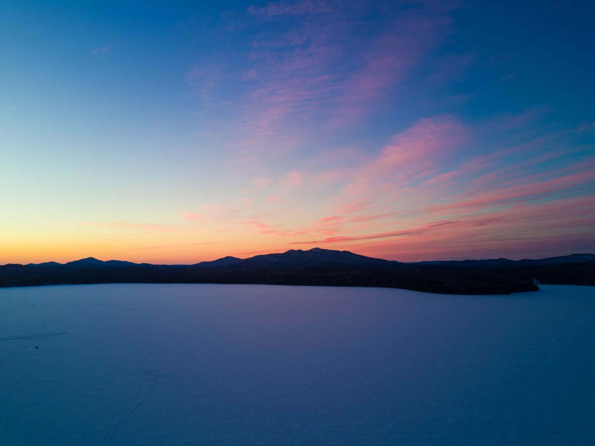 An aerial view of the winter sunset over a frozen Lake Clear.