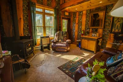 Writer's Cabin living room with lake view and wood burning fireplace