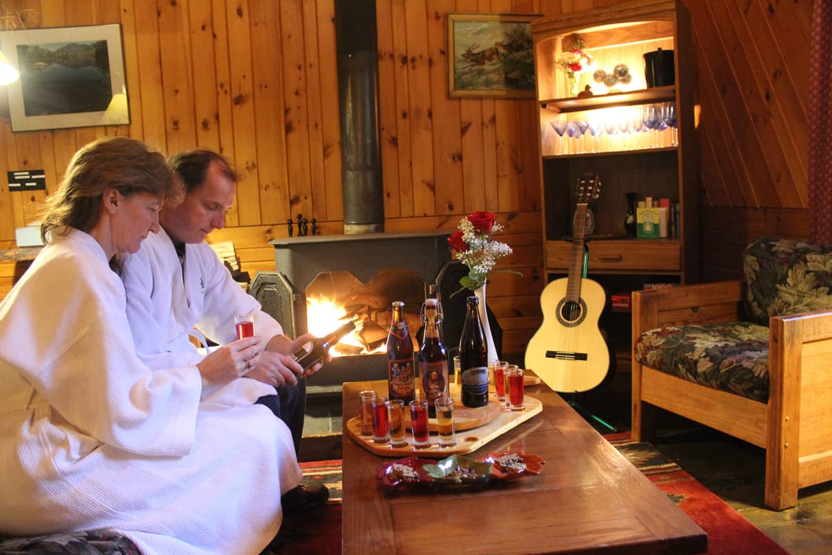 Couple relaxing by the fire in a romantic Adirondack Cabin