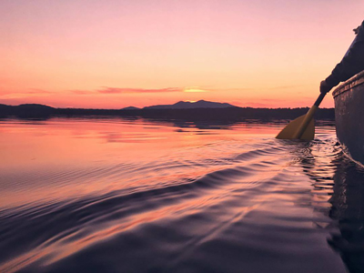 A colorful sunset over St. Regis Mountain during a quiet canoe paddle on a calm Lake Clear at the Lake Clear Lodge & Retreat.
