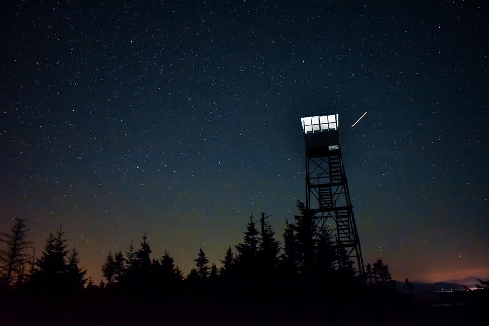 Image Credit: Friends of St. Regis Mountain Fire Tower. The St. Regis Fire Tower Lighting in 2019 with a starry, clear sky in the background.