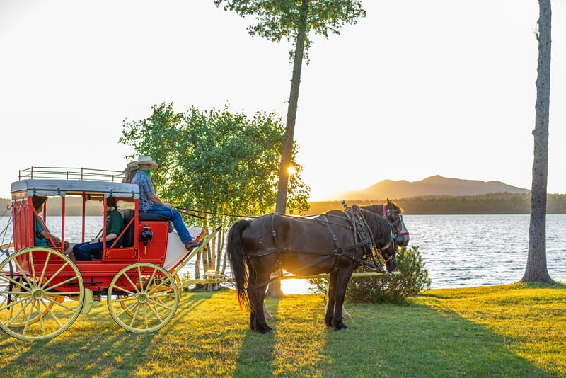 1850s Stagecoach and Percheron Draft Horses Fly and Jasper at the Lake Clear Lodge Lakefront with a sunset view.