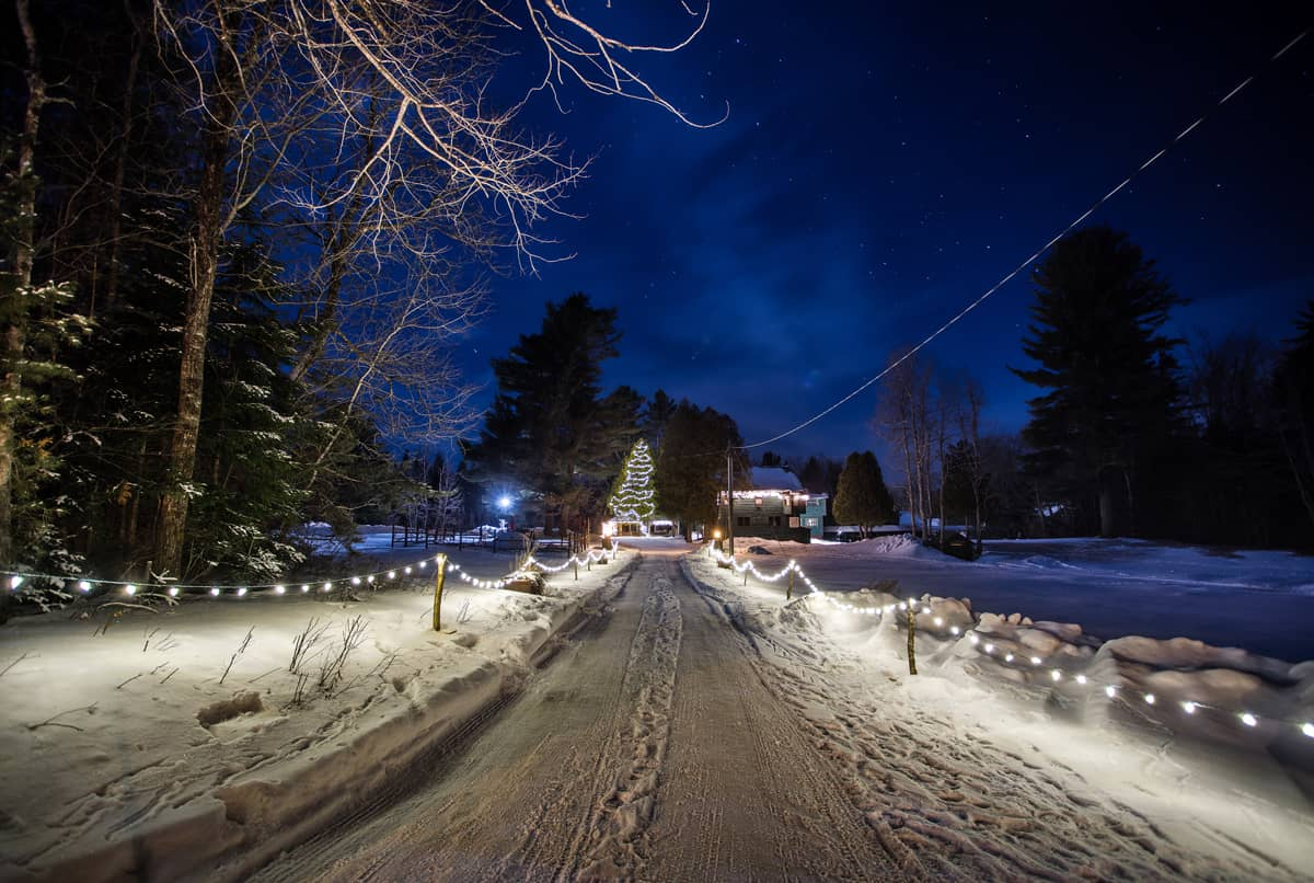Main Lodge Driveway during the winter. White Christmas lights line the roadway at night as the 1886 Main Lodge stands in the distance.