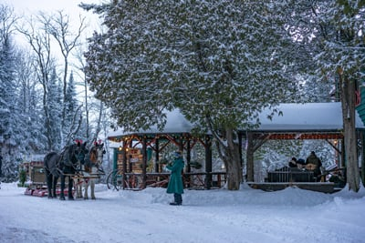 Percheron Draft Horses stand by the 1886 Main Lodge Gazebo with hand-crafted sleigh in tow at the Lake Clear Lodge & Retreat.