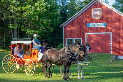 Guests' sit in an 1850s Henderson Stagecoach pulled by draft horses in front of the original 1886 Stagecoach Barn at the Lake Clear Lodge & Retreat.