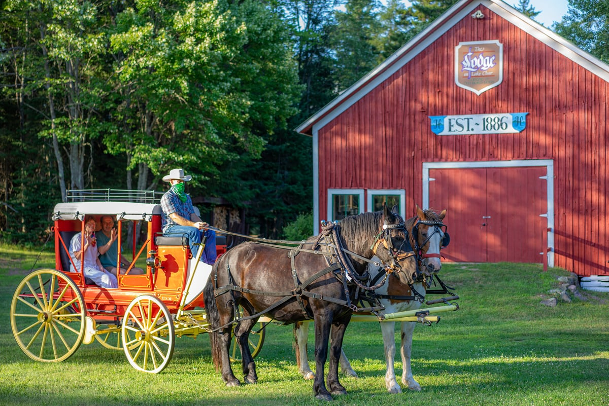 Guests sit in an 1850s Henderson Stagecoach pulled by draft horses in front of the original 1886 Stagecoach Barn at the Lake Clear Lodge & Retreat.